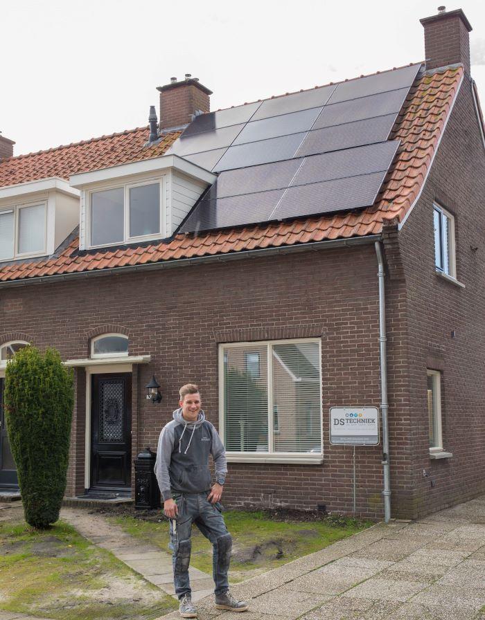 Desley voor zijn woning met een dak vol zonnepanelen