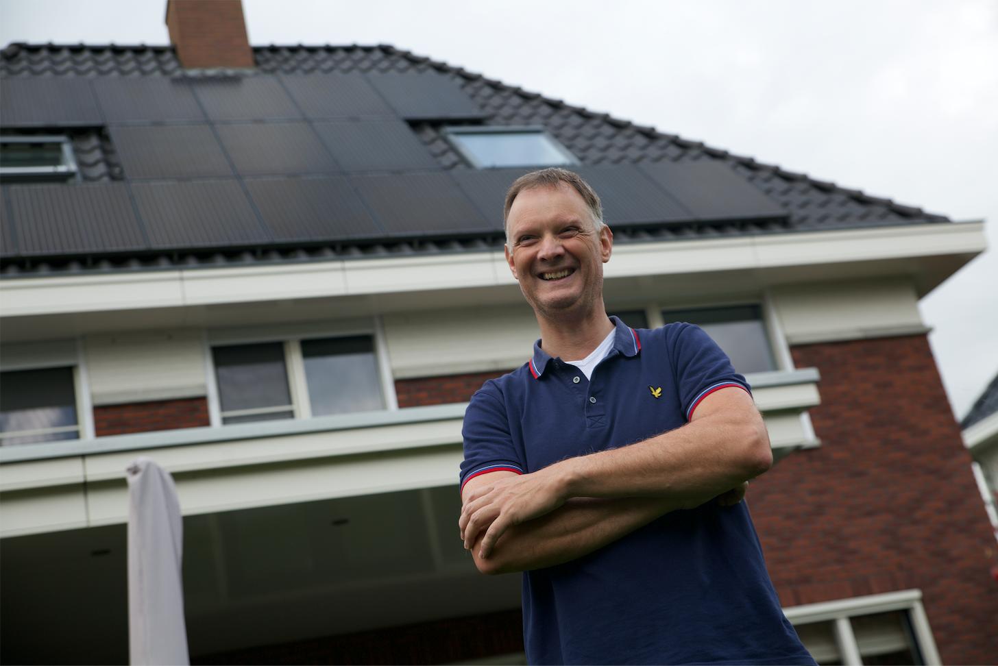 Michel voor zijn woning met zonnepanelen op het dak